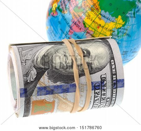 Rolled US Dollars infront of the world isolated on white background.