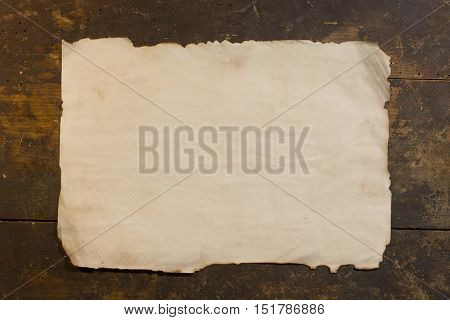 Sheet of the old rough paper on wood background