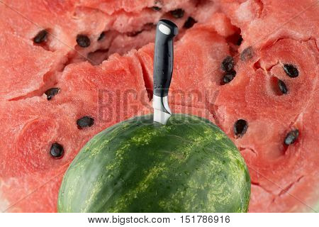 Riped watermelon with knife and red meat background.