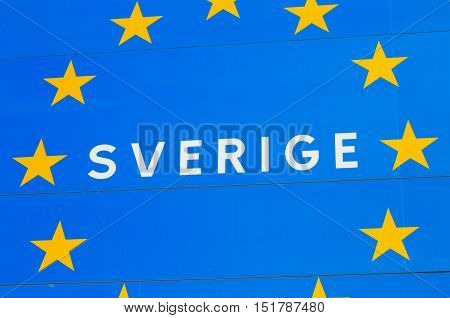 Close up of a road sign at the border to a EU member state Sweden with the Swedish Sverige for Sweden incircled by golden stars on blue background.
