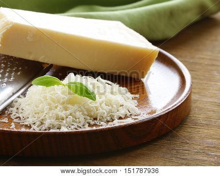 grated and whole parmesan cheese  on a wooden table