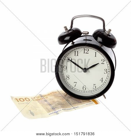 A black alarm clock with happy face on a one hundred Kroner Danish money banknote isolated on white background.