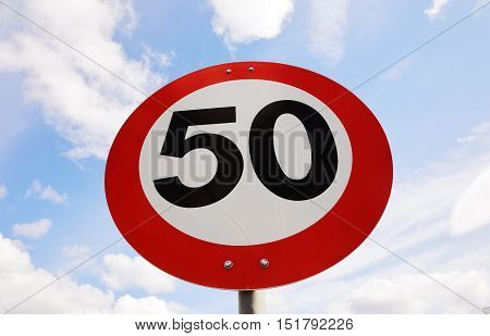 Norwegian speed limit 50 road sign at a low angle view.