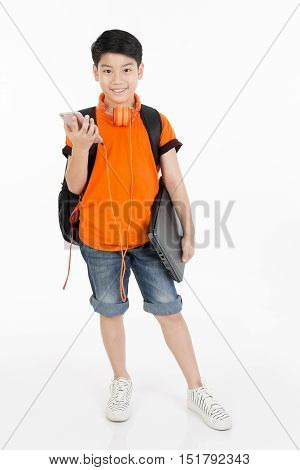 Happy asian boy using cell phone and holding laptop on white background .