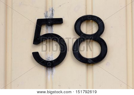 Number fifty eight on yellow wooden wall.