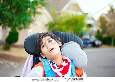 Disabled ten year old boy sitting in wheelchair outdoors looking up into sky thinking
