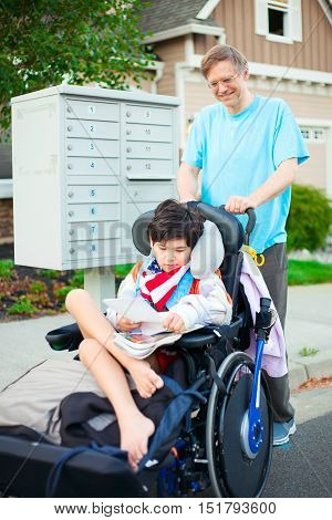 Disabled ten year old boy in wheelchair getting mail from mailbox outdoors with father