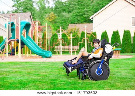 Biracial ten year old disabled boy in wheelchair sitting at a park by a playground smiling in chair