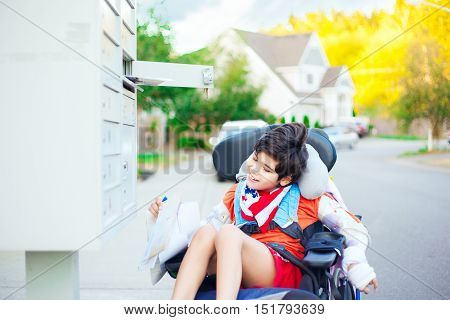Disabled ten year old boy getting mail from mailbox outdoors