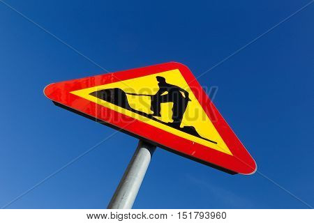 Warning sign for road works against blue sky.