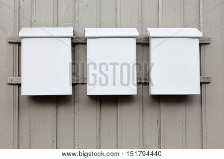 Three white mailboxes of sheet metal mounted on a gray wooden wall.