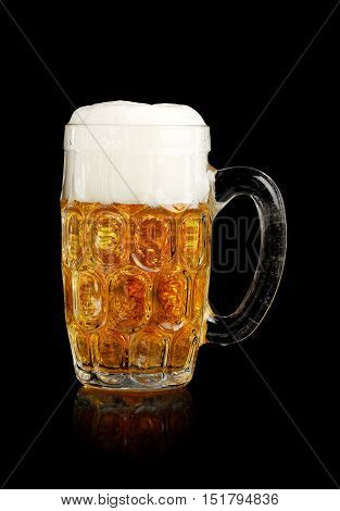 Beer stein with foamy beer isolated on black.