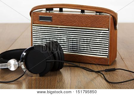 Headphones And Old Radio On Wooden Surface