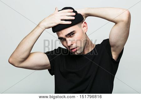 Studio portrait of handsome man putting his hat on, while looking at camera frowningly on white background.