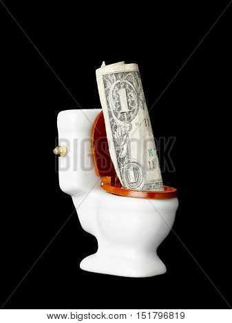 One US one dollar bill in the toilet isolated on black.