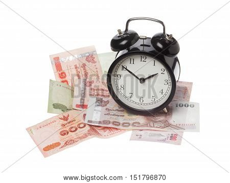 One black alarm clock on Thai baht banknotes isolated on white.