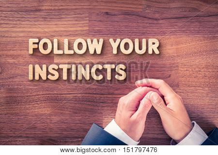 Follow your business instincts concept. Businessman and text Follow your instincts made from wood.