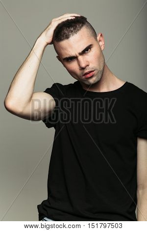 Man on grey studio background with hand on his hair