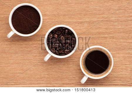Coffee beans ground coffee and cup of brewed coffee on rustic wooden table view from above with space for text