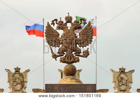 Coat of arms Russian Federation. Coat of arms on background of parapet administrative building government with USSR symbols, flags of Russia and Belgorod region. Focus on the two-headed eagle.