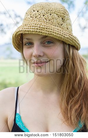 Beautiful young long haired natural woman with no make up wearing a hat oudoors looking at camera