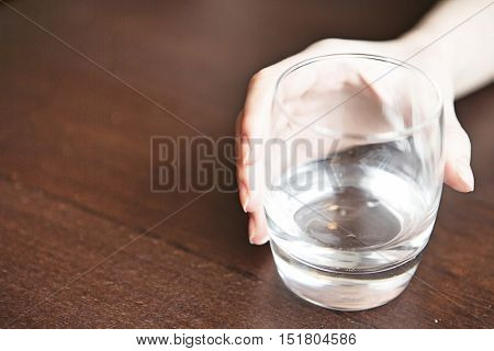 hand holding glass of water on table