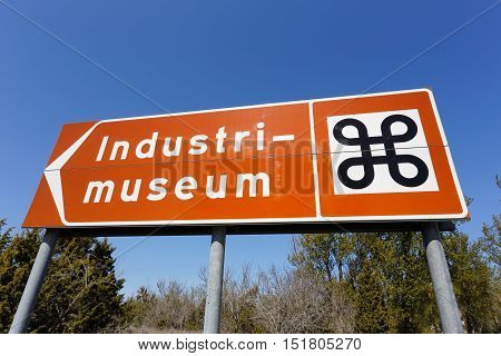 Swedish road signpost pointing to an industrial museum (in Swedish