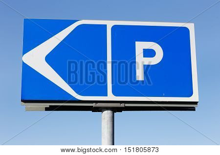 Close-up of direction sign to car parking on blue sky.