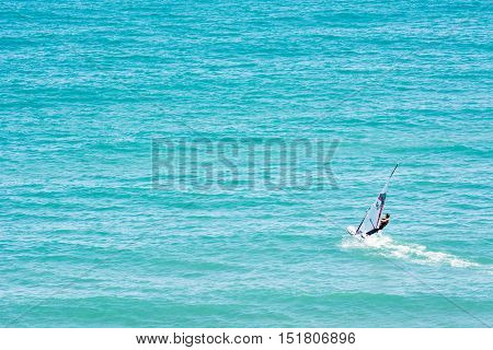 A person alone doing windsurf in the sea