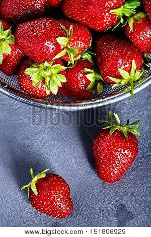 Washed strawberries in sieve with two fresh and juicy strawberries near it on stone background. Top view