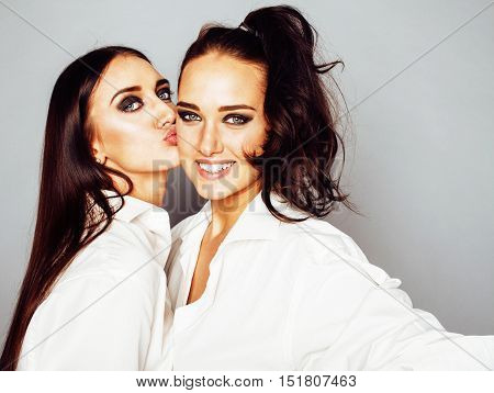 two sisters twins posing, making photo selfie, dressed same white shirt, diverse hairstyle friends, lifestyle people concept