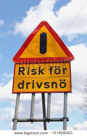 Swedish road sign for other danger with additional sign danger of drifting snow.