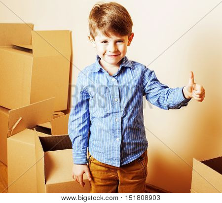 little cute boy in empty room, remoove to new house. home alone emong boxes, lifestyle people concept close up