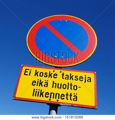 Finnish road sign parking prohibited with an additional panel Does not apply to taxis and service vehicles against blue sky.