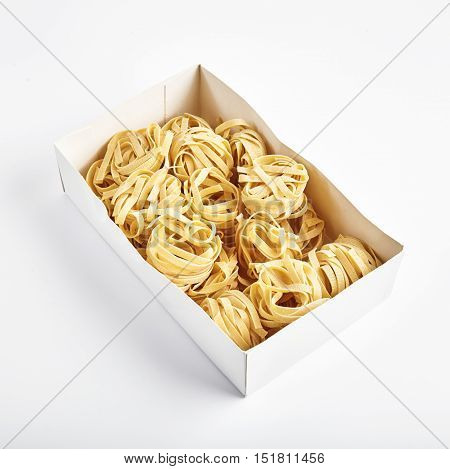 Uncooked rolled traditional italian pasta in white carton box. Portions of raw fettuccine or tagliatelle or pappardelle. Dry pasta from whole wheat flour. Isolated on white background.