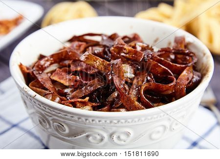 Tasty egg noodles with bacon bits and fried Chinese cabbage in a sauce of soy sauce and spices in white, rustic bowl. Towel and fettuccine nest on the background. Close-up, shallow depth of field