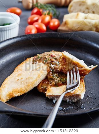 Tasty chops from chicken fillet with sauce of cognac, meat broth and capers on black, rustic dish. Slices of fresh bread, cherry tomatoes, pepper mill and bowl of greenery in the background.
