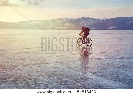 Ice biker traveler with backpacks on bike on ice of Lake Baikal. Against the background of sunset sky ice surface. Winter sport concept. Cycling.