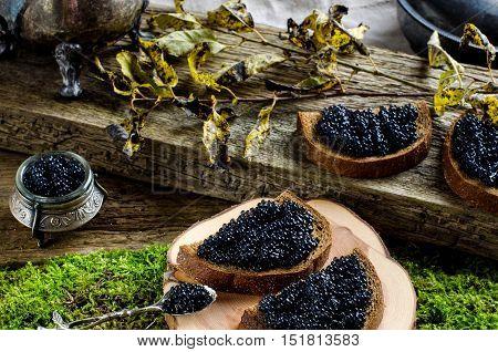 Black caviar on dark bread. The old Board moss. Silverware. Vintage style. Russian food.