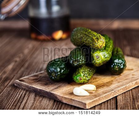 Pile of pickled cucumbers in soy sauce and rice vinegar on cutting board on wooden table, cloves of garlic near it. Jar with the marinade behind. Chinese recipe. Shallow depth of field, closeup shot