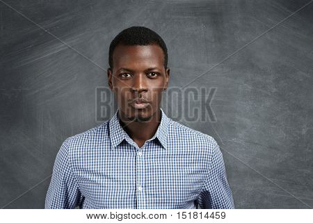 Portrait Of Handsome Young African School Teacher Wearing Checkered Shirt Getting Ready For Lesson,