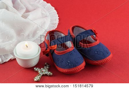 Christening background with booties candle and Christian cross pendant