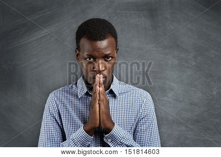 Portrait Of Handsome Dark-skinned Student Holding Hands In Prayer, Looking Worried And Impatient, An