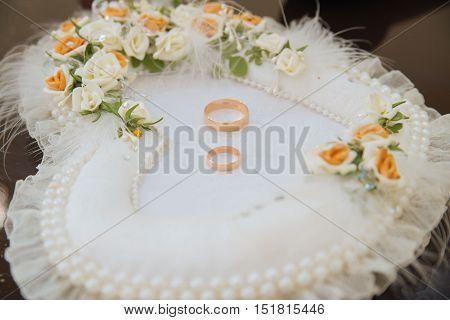 Gold wedding rings lie on the pincushion