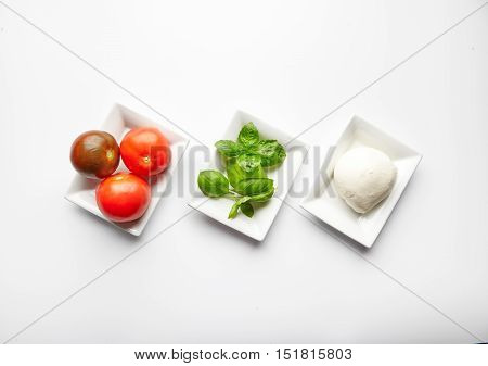 Fresh ingredients for Italian Caprese salad in white plates. Basil leaves, mozzarella cheese and juicy tomatoes. Mediterranean cuisine. Traditional Italian dish. Isolated on white background