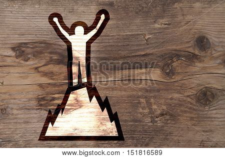 Illustration of man on top of mountain on brown wooden background