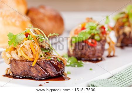 Meat medallions with vegetables and greens close up