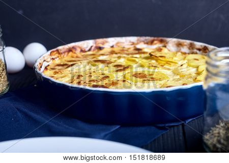 Potato gratin with cream, eggs and cheese on dark wood background and spices in jar.