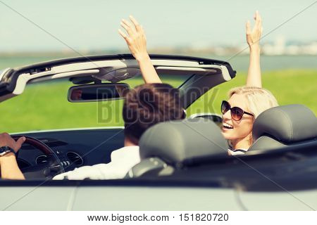 transport, road trip, leisure, couple and people concept - happy man and woman driving in cabriolet car outdoors