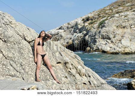 beautiful young skinny model posing on nature with black bikini